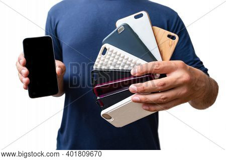 Man Holding A Choice Of Multicolored Plastic Back Covers For Mobile Phone. Smart Phone Protector Acc