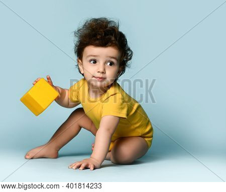 Small Cute Smiling Curly Hairy Baby Boy Toddler In Yellow Comfortable Jumpsuit Sitting On Floor With