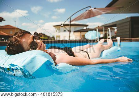 Young Woman In Bikini On Float Mattress In Round Above Ground Swiming Pool In Backyard