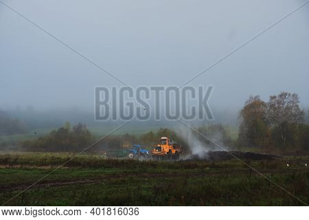 Selective Focus, Large Farm Tractors Carry Manure And Other Steaming Fertilizer Across The Fields