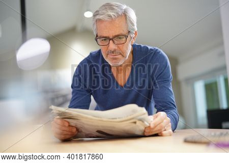 Senior man at home relaxing and reading newspaper