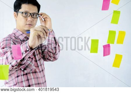Asian Businessmen Are Sharing Their Thoughts On The Glass Wall. Brainstorming Concept. Sticky Note O
