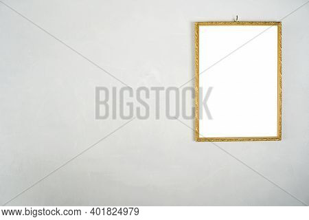 Golden Picture Frame Hanging On A White Cement Wall.  White Label Floor For Text, Images, Advertisin