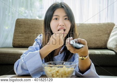 Asian Women Are Watching Tv At Home. She Is Using The Remote To Change The Channel, She Is Happy To