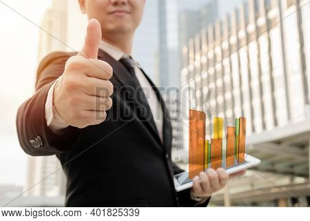 Businessmen Are Holding Their Thumbs To Express Joy. By Holding The Tablet And It Shows The Graph Da