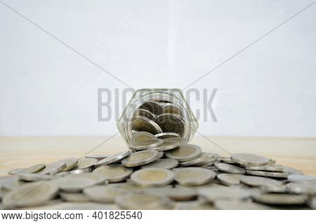 Saving For The Future Concept. A Glass Piggy Bank With Coins Piled A Lot On The Table. Planning, Inv