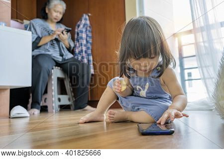 Granddaughter And Grandmother Both Are Using A Smartphone At Home. Future Family Conditions That Use