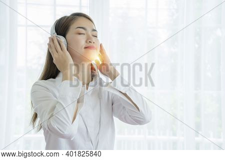 Lovely Asian Girl She Likes Listening To Music. She Listens To Music With Headphones. Wear White Clo