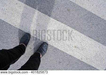 Men Who Are Walking Across The Crosswalk, His Shadow Stretched Out.