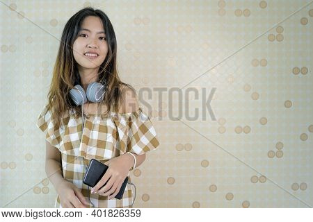 Asian Women With A Cute, Bright, Cheerful Appearance. She Is Listening To Music From Her Smartphone,