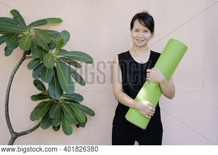Sporty Yoga Girl With Yoga Mat Wearing Training Clothes Over Vibrant Background. Smiling Women Yoga