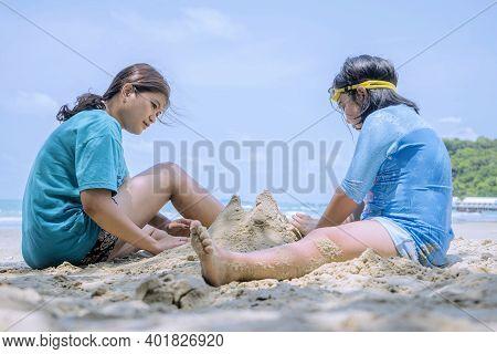 Asian Mothers And Daughters Are Excited About In The Sea, Playing Sand Piles. The Good Relationship