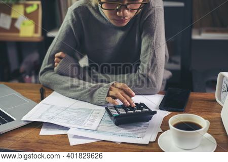 Season To Pay Tax, Budget, And Tax Planning Concept. Business Woman Wear Glasses Calculating Annual