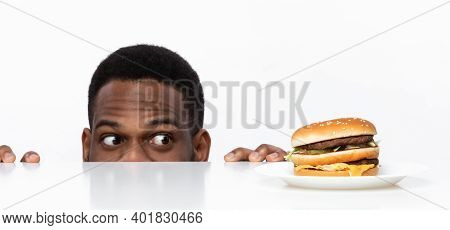 Funny Hungry African Guy Looking At Tasty Burger On Desk Having Food Craving Posing In Studio On Whi