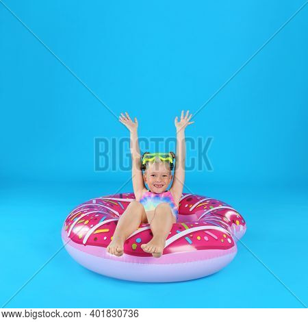 Cute Little Child In Beachwear With Inflatable Ring On Light Blue Background