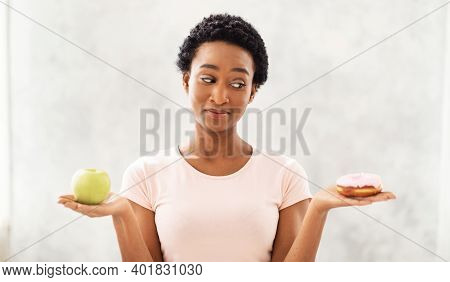 Healthy Diet Vs Junk Food. Pretty Black Lady Holding Apple And Donut In Her Hands, Tempted To Eat De