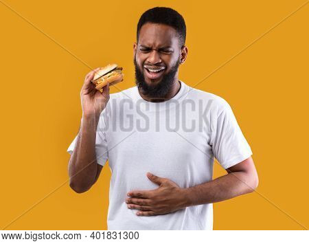 Unhealthy Eating. Black Man Suffering From Stomachache After Burger Touching Aching Stomach Standing