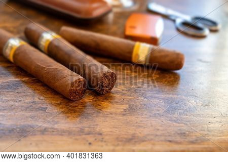 Cuban Cigars And Smoking Accessories On Wooden Desk