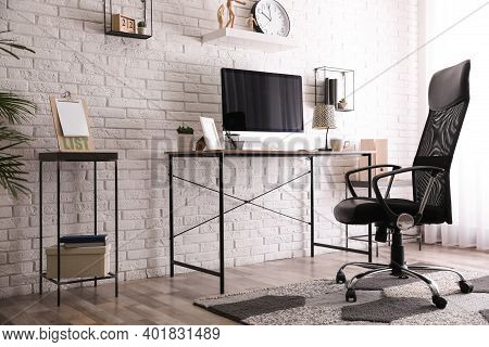 Comfortable Chair Near Desk In Modern Office Interior