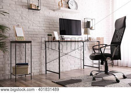 Comfortable Chair Near Desk In Modern Office Interior