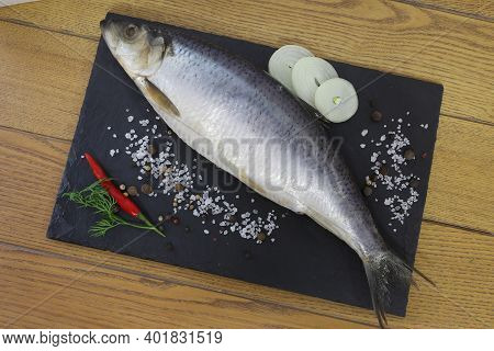 Sea Salt Herring Undivided Lies On A Wooden Board Next To Sliced Onion Rings And Spices