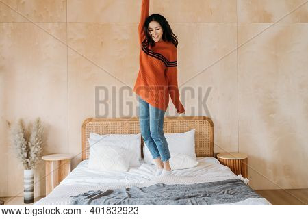 Cheerful Relaxing Asian Ethnic Female In Sweater Smiling And Leaping On Bed While Having Fun At Home