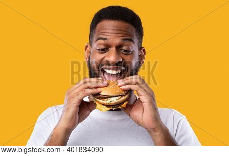 Funny Hungry Black Guy Biting Burger Eating Junk Food Standing Over Yellow Studio Background. Africa