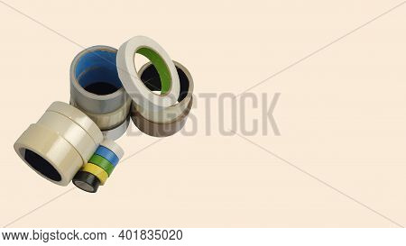 A Heap Of Packing Tape And A Masking Tape On An, And Construction Clear And Brown Adhesive Tape Are