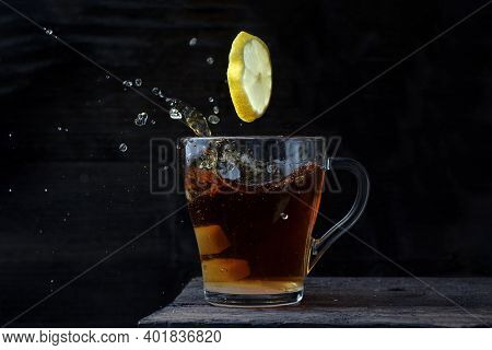 Lemon Flew Into A Tea Mug With Strong English Tea And Sugar On A Black Wooden Background With A Lot