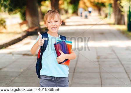 Happy Boy With Backpack Going To School. Child Of Primary School. Pupil Go Study With Backpack And B