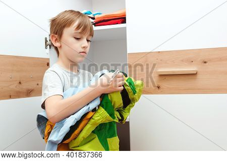 Kid Makes Order In His Wardrobe At Home. Child Organizing Clothes In The Closet. Order In The Closet