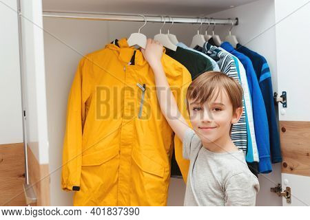 Boy Taking Jacket From Hanger Stand. Wardrobe With Child's Clothing.