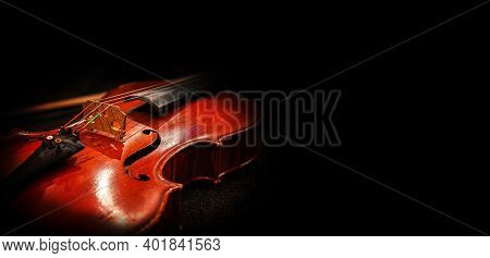 Violin On A Dark Background. An Old Violin In Beautiful Lighting.