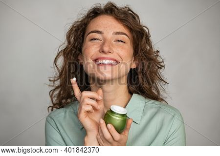 Young woman applying cream on her face full of freckles. Beauty girl holding biological moisturizer jar while looking at camera. Portrait of casual woman with daily lotion isolated on grey background.