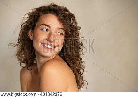 Portrait of smiling girl enjoying beauty treatment on beige background. Beautiful natural woman looking at copy space, spa and wellness concept. Carefree laughing woman with bare shoulders isolated.