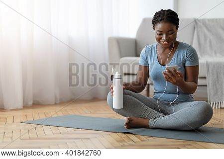 Smiling Black Lady Relaxing With Smartphone On Yoga Mat After Training At Home, Wearing Earphones, L