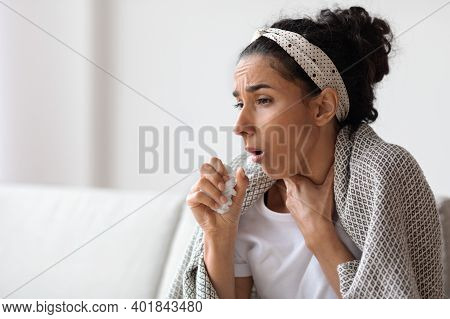 Sick Young Brunette Woman Covered In Blanket Coughing And Looking At Copy Space, Sitting On Couch In