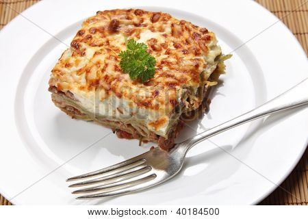 A slice of homemade lasagne verdi on a plate with a fork, high angle view poster