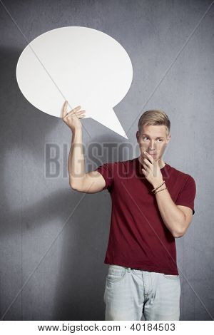 Serious man thinking while holding white empty speech balloon with space for text isolated on grey background.