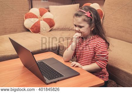 Little Girl Looks At Her Laptop And Bites Her Nails While Sitting At Home.