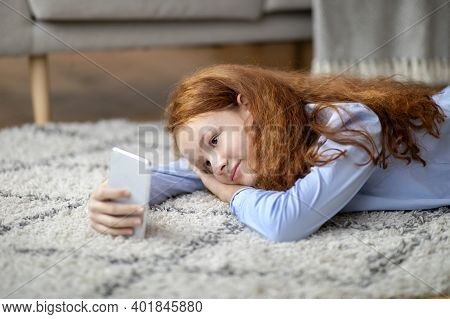 Spending Time At Home. Portrait Of Cal Smiling Red-haired Genz Tween Girl Using Her Mobile Phone, Wa