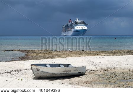 The View Of An Old Little Boat On Grand Cayman Island Seven Mile Beach And A Cruise Liner In A Backg