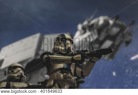 JAN 3 2021: Low angle view of a Star Wars 501st Stormtrooper Commander (Vader's Fist) with an At-AT in the background - Hasbro action figures