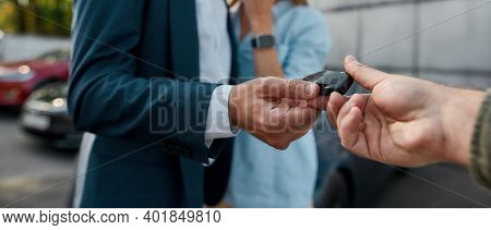 Close Up View Of Car Keys Given To Businessman By Sales Manager In Luxury Auto Showroom, Panorama. C
