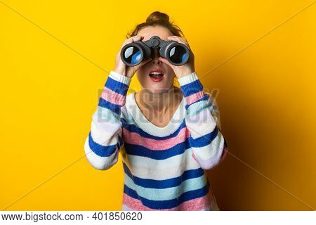 Young Woman In Sweater Looking Through Binoculars On Yellow Background