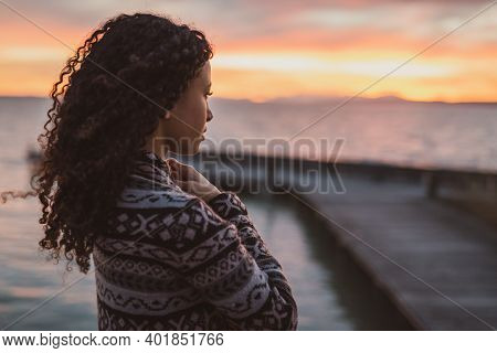 Young African American Woman Is Standing On The Promenade At The Lake, Looking Thoughtfully Towards