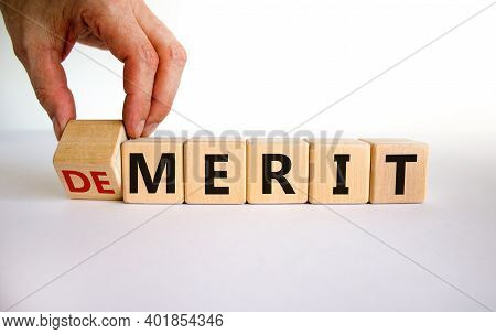 Demerit Or Merit Symbol. Male Hand Flips The Wooden Cube And Changes Words 'demerit' To 'merit'. Bea