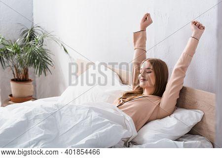 Awake And Joyful Woman In Satin Pajamas Stretching In Bed