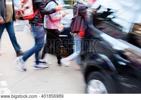 People Crossing A Street Between Cars