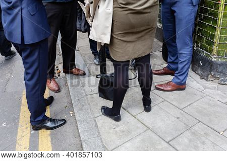 Legs Of Business Men And Woman Standing Together On A Sidewalk